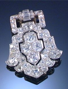 DIAMOND CLIP BROOCH, 1930S Designed as an open work shield-shaped plaque set with circular- and single-cut, cushion-shaped and baguette diamonds.