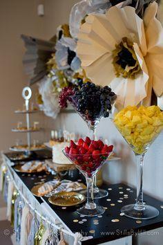 Glittery Family Milestone Celebration - fruit display in giant martini glasses on dessert table.