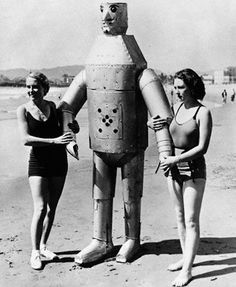 Women pose with a robot on the beach, 1925.