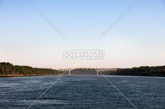 view of a ocean with bridge in background. - Image of a rippled sea with bridge and clear sky in background.