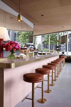 Bill Granger opens a new restaurant in London: 1970s table lamps sit on the rounded pink tiled and brass bar. Guests sit on diner-style leather and brass high stools.