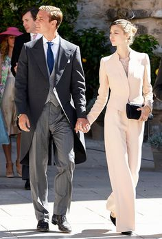Princess Beatrice Borromeo wears a light pink matching suit with a black clutch, black pointed toe heels and gold jewelry.