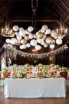 white and gold paper lanterns hanging above reception at lodge venue