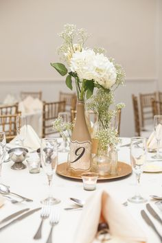 DIY wine bottle centerpiece with hydrangeas and blush roses. Table setting.