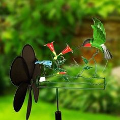 Hummingbird Whirligig is wind powered and moves with the slightest breeze. Metal sculpture features a hovering sprite feeding at trumpet flower with dragonfly. When wind moves the propeller, hummingbi