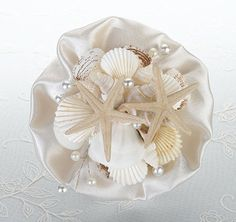 Coastal Sea Shell Bouquet ~ For beach-themed and destination weddings, this seashell bouquet makes a great accessory for the bride or bridal party to hold walking down the aisle. The clear acrylic handle holds a bouquet made of an ivory satin ruffle and a collection of different seashells and starfish. Makes a great keepsake to display after your wedding day!