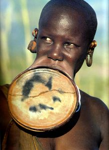 In some African tribes, young girls stretch their lips with round wooden or clay plates and wear them throughout their lives. Their lips eventually get so elastic that the plate can be taken out and put back on easily. The plate must always be in while in the presence of men and can only be taken out when sleeping or around other women. The bigger the plate the more beautiful she is considered.