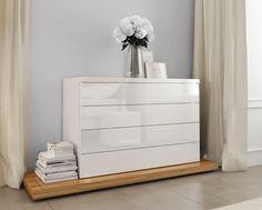 Bílá komoda i noční stolky jsou zdobené lesklou dýhou zebráno.