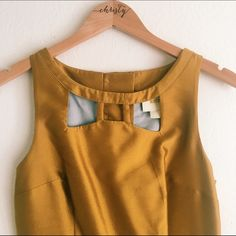 Anthropologie (Maeve) Gold Dress Beautiful structured gold dress with bow cutout detail on neck and included pockets! Shell: 50% Silk, 50% Wool. Lining: 100% Cotton Anthropologie Dresses Midi