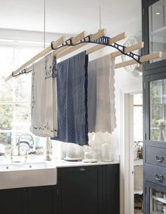 The pulley maid deluxe ceiling clothes airer drying rack hanging in a traditional country kitchen setting. The rack ends are white and the wooden laths pas through them as the washing is hung to dry in the laundry utility room.