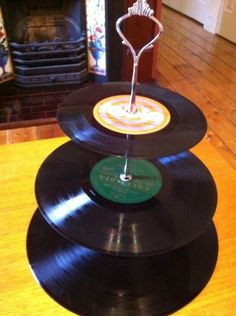 Upcycled Vinyl Cake Stand    Simply seal the labels with clear varnish or nailpolish!  Buy a set of tiered handles online or at a pottery shop.  Put together!  Records can be wiped clean (water resistant)!