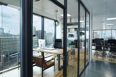 This city glass boxed office wouldn't look out of place in a forest-like office space with the stylish wooden interior. A comfy leather seat sits in front of the desk whilst a more professional leather desk chair sits behind. The full length windows provide panoramic views of the cit