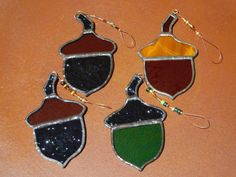 These Stained Glass Acorns come in this group of 4. There are 2 that are made with dark textured Brown bottoms, and Amber colored caps. There is 1 with a Green bottom, and a dark textured Brown cap. The final Acorn is made with 2 different shades of Amber colored glass. The Acorns all have a Copper colored finish. They all measure around 3 3/4 L x 2 1/4 W. They all hang from beaded wire. These can be used in so many ways. These can decorate your window, decorate a gift, a christmas tree, a…