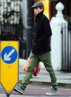 Covering up for the cold, Eddie Redmayne puts on a coat and driver's cap with casual Converse sneakers.