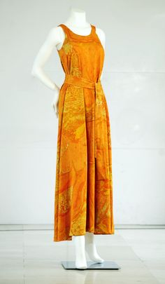 Woman's sleeveless dress in knitted polyester printed with mottled design using shades of orange and yellow, low scooped neckline front and back, centre back fastening, loose A-line shape extending to floor length, unlined. British, garment design possibly by Janet Medd or Eric Sporrong, for Bernat Klein Design, 1975-76.