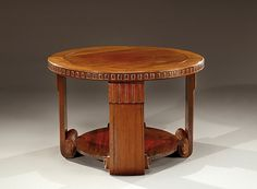 MAURICE DUFRENE, attribué à Table basse en palissandre et acajou massif présentant deux plateaux circulaires moulurés et superposés à décor en bordure de motifs géométriques évidés.