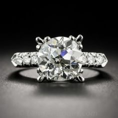 Bright, brilliant, blazing and amazing! Although weighing in just five points shy of 4 carats, this exuberant ultra-sparkler appears even larger and more impressive due to its striking, flared four-cornered setting, handcrafted in platinum - circa 1950s. The dynamic diamond sparkles mightily between angled rows of small round brilliant-cut diamonds leading to a sleek knife-edged ring shank. Accompanied with a GIA Diamond Grading Report stating: K color - SI1 clarity. Currently ring size 7…