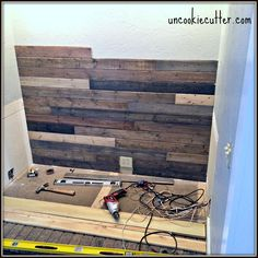 I created this mixed wood wall with cheap wood paneling from Lowes, leftover stain and paneling nails for around $40. UncookieCutter.com