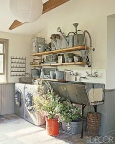 """""""The vintage industrial ambiance of this laundry room from Elle Décor tops my list!  I just love how the garden room and laundry room can live together so harmoniously.  The deep trough-like sink, vintage bottle drying racks (perfect for drying intimates – genius!), and the fantastic collection of galvanized watering cans make me swoon."""""""
