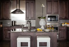 Lee Kleinhelter's Atlanta home: gorgeous kitchen with chrome backsplash and rich cabinetry, perfectly accessorized w/ Jonathan Adler utopia vase