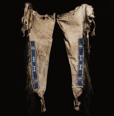An Early Pair of Upper Missouri River Beaded Hide Leggings, probably Blackfoot, each painted with a series of horizontal black stripes against the natural ground, overlaid with a hide strip, sinew sewn in white and bright blue glass pony beads, with hourglass and pronged devices, trimmed on the outer edge with human and horse hair pendants, wrapped in porcupine quillwork. lengths approximately 39 in. Sotheby's AMERICAN INDIAN ART 08 MAY 2006. NEW YORK