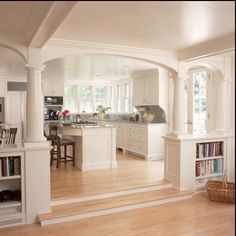 i like the small stairs down into a family room. a living room would be on the left of this picture facing away from the island. the bookshelves on either side of the stairs with the vents underneath. reminds me of Swanson's house! i don't like the columns.