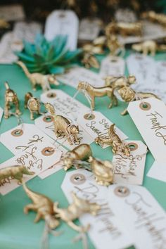 Instead of your standard tent-folded escort cards, attach gift tags to gold figurines. You can spray paint them in your wedding's colors.