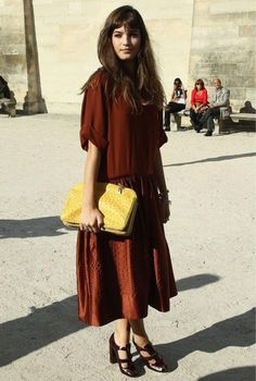 Alma Jodorowsky holds a yellow clutch to add a pop of color to her head-to-toe maroon look