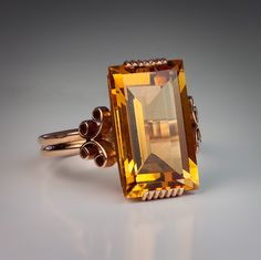 A 14K rose gold geometric ring influenced by industrial design is set with a rectangular citrine( 16 x 10 x 6.15 mm, approximately 6.52 ct) - Soviet, c1960.