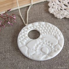 Pure white porcelain pendant by Kim Wallace. This piece was created by rolling a vintage lace doily into the clay whilst wet, leaving the lovely pattern behind. Complemented beautifully by an elegant sterling silver chain.