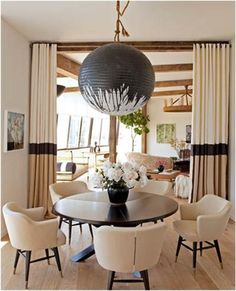 Airy Transitional Dining Room by Trip Haenisch Trip Haenisch combines these elements in this transitional dining room: beige curtains; beige dining armchairs; black vase; curtain room divider; light hardwood floors; modern black light fixture; round dining table; striped curtains.