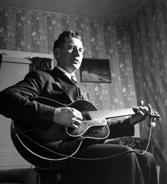 Considered the father of country music, A. P. Carter, singing and playing guitar as he sits at home.