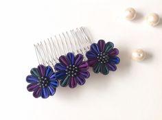 舞妓さんのかんざしに使われる「つまみ細工」。  小さな布を、折り紙のようにたたんで、お花や蝶を作る伝統工芸です。  ふだん使いからパーティまで、ヘアアレンジのアクセントに使える、コームをおつくりしました。  ほとんど黒に近いダークナイトブルーを縁取りに、深緑、藍色、紫、紺、紫紺 の花びらをランダムに使っています。  お花自体は小さなものですが、「二重つまみ」という、生地を重ねて作る手間のかかる技法を用いています。  みっつ並べたお花の、微妙なグラデーションが「オトナかわいい」雰囲気に仕上がりました。  素材:キュプラ お花の直径:約3cm×3個  花芯はつやっとした黒。ブラックベリーのようで美味しそうです。