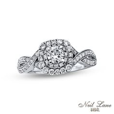 A brilliant celebration of your love, this stunning vintage-inspired diamond engagement ring from the Neil Lane Bridal® Collection will take her breath away. Fashioned in cool 14K white gold, this ring showcases a 1/3 ct. round diamond center stone bordered with a halo frame of smaller round accent diamonds. Additional accent diamonds line the ring's cleverly twisting double shank, while intricate milgrain detailing adds heirloom appeal. Neil Lane's signature is engraved on the i...
