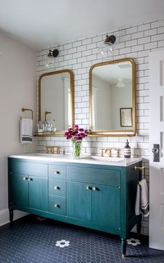A teal blue vanity with brass fixtures warms up a wall of white subway tile set in black grout and a floor of black hex tiles.