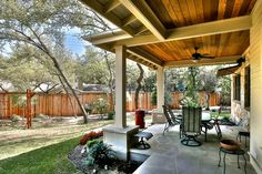 Warm wood paneling covers the ceiling of this porch, shading the outdoor sitting area. A well-manicured yard with a wooden privacy fence completes the design.