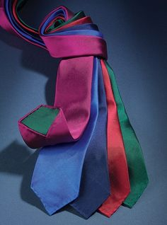 Pure English silk neckties woven with a double warp – one color on face and the complementary color on reverse. Entirely hand sewn with hand rolled edges. Shown left to right: A-fuchsia with forest; C-Persian with midnight; F-navy with new red; G-new red with navy; L-forest with fuchsia.