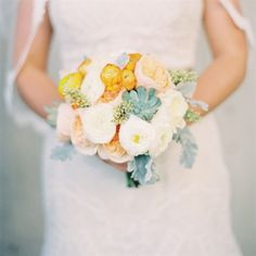 Bride carried which, peach and orange ranunculus, garden roses and succulents.