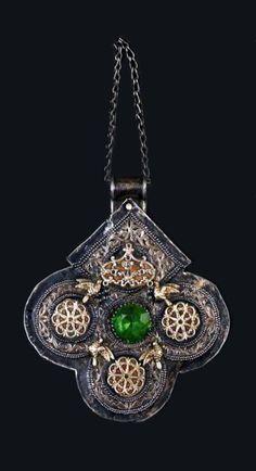 """GRANDE """" FOULET KHAMSA """" EN ARGENT ciselé à décor floral, décorée de trois rosaces ajourées dorées et sertie d'un cabochon de verre taillé au centre d'un pendentif, entre quatre oiseaux dorés. L'envers est également décoré. Avec une chaînette de suspension. Poinçon à la tête de bélier et début du nom de la ville """" Essaouira """". Poids brut : 183g. Essaouira, vers 1925."""