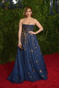 Jennifer Lopez is giving us a glamorous look worthy of her Hollywood status. Wearing a strapless celestial ballgown in midnight blue — by  Valentino's Pierpalo Piccioli and Maria Grazia Chiuri — she wore her new short hairdo back in a slightly curled bob for a very romantic look.