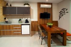 Projeto de Sacada com espaço gourmet, mesa de jantar e painel de Madeira com tv. Decorando Com Classe