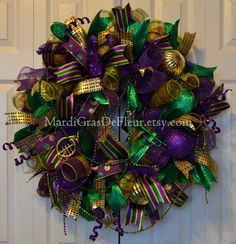 Welles Mardi Gras wreath begins with a work form base decorated with wide deluxe mesh, thin striped mesh, and premium deco mesh. It is adorned with ribbon of 4 different designs. Ornaments and glittered spray coils have been added to take that glitz up a notch. To complete the design multiple strands of beads.