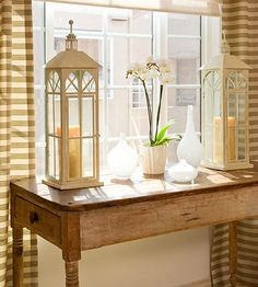 I love the lanterns on the simple wood table - and I only wish I could keep an orchid alive
