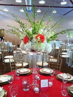 Coral roses, green orchids and white hydrangeas for a stunning tall centerpiece