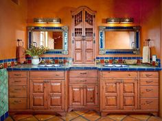 This master bathroom vanity is enriched with Mexican influences, including tin light fixtures and mirrors, colorful Talavera tile on the vanity and sinks, and Saltillo tile flooring. The adobe walls and color palette represent the warm Mexican climate. Design by Classic New Mexico Homes