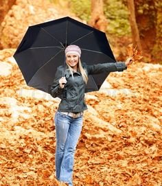 Stock image of 'Photo lovely woman walk under umbrella in rainy day in autumnal park, smiling girl hold in hand bouquet of orange dry leaves, cheerful blond model in stylish hat with black parasol in fall forest'