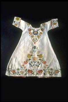 KLEID (KINDER) IN-8682 Kleid (Kinder). Mit bunter Wollstickerei und Seidenbändchen auf Leinen. 1700 - 1800. Masse: Höhe 43 cm. (IN-8682)