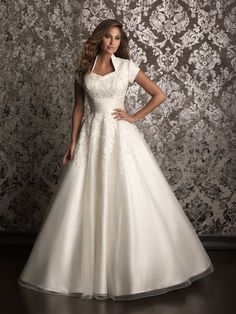 A romantic ball gown in soft tulle.  The bodice is embellished with a lovely lace applique while a ruched satin band defines the natural waist.  (I love this neckline.)  From Allure Bridal.