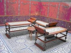 Reconstruction of a triclinium (dining room of a Roman villa) in the Munich Bavarian State Archaeological Collection. The wood and bronze dining couches are based on finds from Pompeii, and Herculaneum ( C1st CE), as is the colour of the simply decorated walls. The mosaic floor is from a Roman villa (C3rd CE) from Kraiburg am Inn.