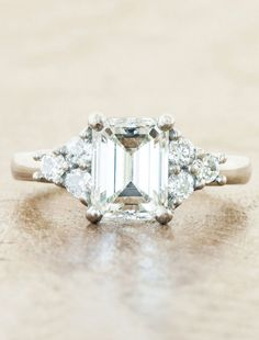 Allison features a stunning 1.51 carat emerald cut diamond flanked by precious, round diamonds on either side.  She's classic and timeless. Sophistication and class all rolled into one.  by Ken & Dana Design.